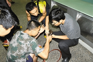消防人员正在帮吴先生取下穿透手指的鱼钩